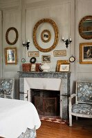 Open fireplace with stone surround in traditional bedroom and gilt frames on wood-panelled wall painted pale grey