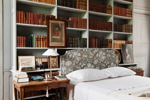 Double bed in front of open-fronted shelving holding antiquarian book volumes