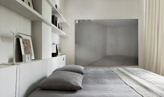 Pillows on modern double bed against wall of fitted shelving with modern artwork on wall in background