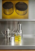 Metal still-life - storage jars on stainless steel worksurface and graphic artwork on wall