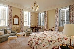 Romantic double room in elegant country-house style with Provençal rose patterns and antique furnishings in traditional hotel