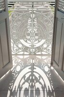 Artistic, white-painted metal lattice in front of French window with grey shutters