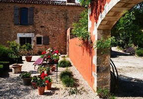 Planters on gravel in Mediterranean garden of country house villa with view of drive through archway