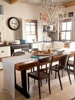 Rustic, wooden dining table with white table runner and assortment of chairs under a light with a nautical light fixture in a country kitchen