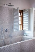 Bathtub and wall with bright, mosaic tiles and open shutters at the window in a modern bathroom