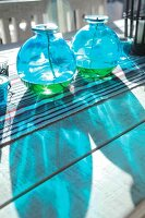 Modern blue glass candles with wicks and oil on a table with a table runner, outside