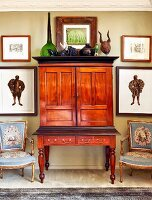 Antique mahogany bureau flanked by Baroque armchairs and framed pictures on wall