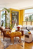 Corner of yellow-painted living room with lounge area and shiny gold sheep sculpture on zebra-skin rug