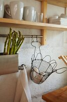 Green asparagus in sink and wire basket of fresh eggs below crockery on shelf