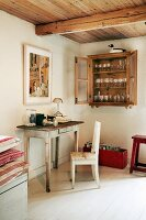 Small secretary table with chair and glasses in wall-mounted cabinet