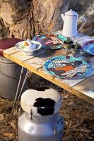 Table with rustic wooden table top, painted plates and vintage milk churns with animal-skin cushions in garden