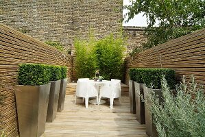 Designer terrace with white outdoor furniture and topiary box bushes in planters against wooden walls