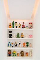 Plastic figurines on shelving in niche with indirect lighting