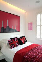 Red patterned bedspread on bed and modern picture on white wall with indirect lighting
