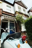 Vintage scooter parked in front of English-style terraced house
