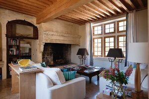 New wooden ceiling within old walls - interior with white sofas in front of large inglenook fireplace