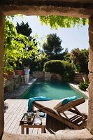 View though stone window frame of sun lounger on wooden deck next to Mediterranean pool