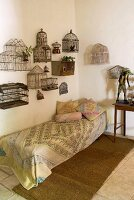 Vintage birdcages mounted on wall above couch in corner of simple room