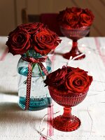 Red roses in glasses and jar