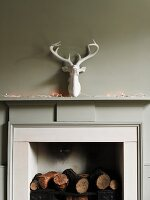 Fireplace decorated with logs, fairy lights and fake stag's head