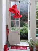 Red decorative bells of honeycomb paper hanging on door