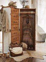 Trunk-style wardrobe with handbag and items of clothing