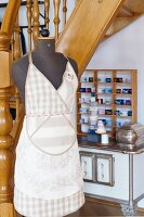 Tailor's dummy wearing linen apron in sales room; shelves of rolled, fabric ribbons in background