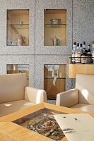 Elegant armchairs and table in front of bar and display case with separate, glass-fronted compartments