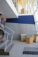 People on steps in open-plan foyer with lounge furniture