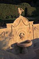 Stone wall in garden with sculpture and carved ornamentation above fountain bathed in evening sun