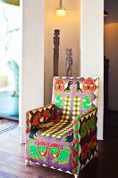 Ethnic-style armchair in front of African wooden figures