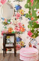 Mirror on wall with floral wallpaper above side table and pouffe