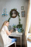 Young woman seated at small console table