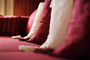 Detail of Bordeaux red and white cushions with tassels on red sofa (Schloss Schauenstein)