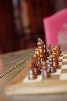 Wooden chess pieces on chessboard on old table with blurred pink chair in background (Schloss Schauenstein)