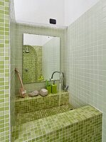 Sink integrated in niche with green mosaic tiles