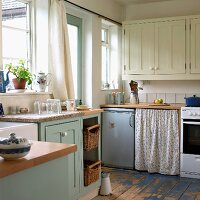 Country-house style kitchen-dining room with cream and pastel blue fronts, retro fridge and floral curtain