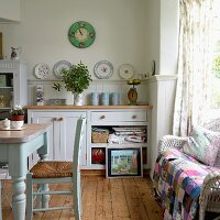 Table, rush-bottomed chair and patchwork blanket on wicker sofa in cosy, country-house kitchen