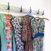 Colourful, floral dresses and pinafores hanging on old, vintage-style coat rack