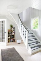 White, wood-panelled foyer with open-plan staircase in country house