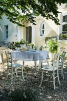 Table set with white cloth and crockery and wooden chairs on gravel surface in front of old country house