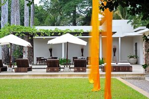 Lengths of orange fabric hanging over lawn; loungers and parasols on terrace with roofed area in background