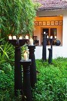 Lit candles on black, floor-standing candlesticks in garden