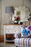 Lamp with lampshade and vase of flowers on cabinet in front of sun-shaped mirror