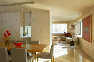 Dining table in modern retro style in front of a room divider and look in cozy living area