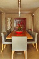 Padded chairs with light gray relation to wooden table in the dining room with retro flair