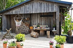 Tree stump stools, table and stacked firewood on terrace of wooden cabin