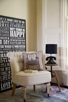 Upholstered armchair with scatter cushion in front of lettered artwork next to antique telephone and lamp on side table in corner of living room