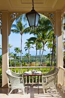 White rattan chairs at set table on colonial-style veranda with view into garden of palm trees
