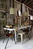 Festively set table below pendant lamps in front of DIY wooden wall made from window frames and wooden panels in barn-like room